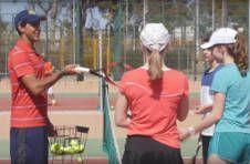 Thumbnail Trainer und internationale Teilnehmer beim Verbessern der Tennis-Techniken
